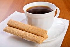 Tasse Kaffee mit Sahnebeutel der Waffel. Stockfotos