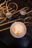 Tasse Kaffee mit Salz- und Pfeffersch?ttel-apparat auf Tabelle im Kaffeestubecaf? lizenzfreie stockbilder