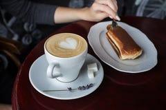 Tasse Kaffee mit Schaum- und Tiramisukuchen Lizenzfreie Stockbilder