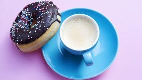 Tasse Kaffee mit Schokoladendonut auf rosa Tabelle lizenzfreie stockbilder