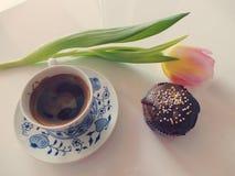 Tasse Kaffee mit Schokoladenmuffin- und -tulpenstillleben lizenzfreie stockfotos