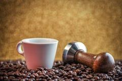 Tasse Kaffee mit Stampfer und Kaffeebohnen auf Goldhintergrund, Produktfotografie für Kaffeestube Stockbilder