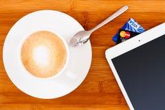 Tasse Kaffee mit Tablette stockfotos