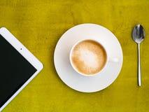 Tasse Kaffee mit Tablette auf grünem Hintergrund Lizenzfreie Stockfotografie