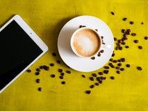 Tasse Kaffee mit Tablette auf grünem Hintergrund Stockfotos