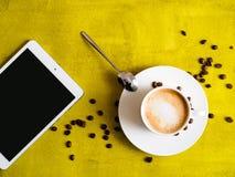 Tasse Kaffee mit Tablette auf grünem Hintergrund Stockfotografie