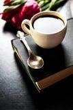 Tasse Kaffee mit Tulpe und Buch auf schwarzem Hintergrund Lizenzfreie Stockfotografie