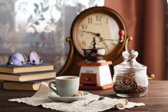 Tasse Kaffee mit Untertasse mit Tasche mit Kaffeebohnen auf Schwarzem Lizenzfreie Stockfotografie