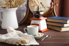 Tasse Kaffee mit Untertasse mit Tasche mit Kaffeebohnen auf Schwarzem Stockfoto