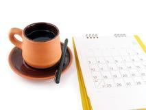 Tasse Kaffee mit Untertassen- und Tischkalender mit den Tagen und Daten im Juli 2016 lokalisiert auf weißem Hintergrund Lizenzfreie Stockfotos