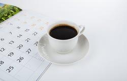 Tasse Kaffee mit Wandkalender auf Weiß Stockfotografie
