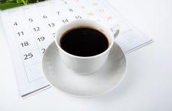Tasse Kaffee mit Wandkalender auf Weiß Lizenzfreies Stockbild