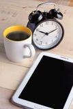 Tasse Kaffee mit Wecker und intelligentem Telefon stockfoto