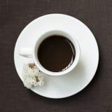 Tasse Kaffee mit weißer Blume auf einer braunen Tischdecke Stockbild