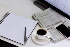 Tasse Kaffee mit Zeitung, Computer und Smartphone auf weißem ta Stockfotografie