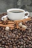 Tasse Kaffee mit Zimt, Sternanis, Muskatnuts und Kaffeebohnen stockfotografie
