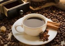 Tasse Kaffee mit Zimt und Kaffeebohnesternanis Stockfotos