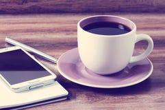 Tasse Kaffee, Notizblock, Stift und ein Smartphone Lizenzfreie Stockfotografie
