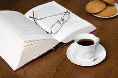Tasse Kaffee, Plätzchen, altes Buch u. Gläser Lizenzfreie Stockfotografie