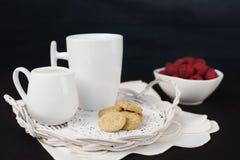 Tasse Kaffee, Plätzchen ein Krug Milch auf einem Strohbehälter Eine Schüssel mit Himbeeren Schwarzer Hintergrund Stockfotos