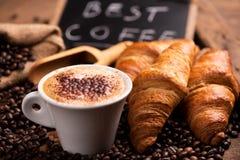 Tasse Kaffee umgeben durch Kaffeebohnen stockfotografie