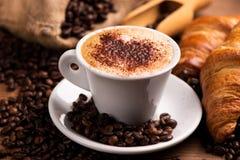 Tasse Kaffee umgeben durch Kaffeebohnen lizenzfreies stockbild