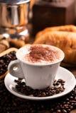Tasse Kaffee umgeben durch Kaffeebohnen lizenzfreies stockfoto