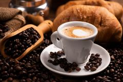 Tasse Kaffee umgeben durch Kaffeebohnen lizenzfreie stockfotografie