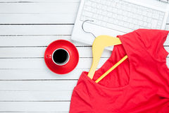 Tasse Kaffee und Aufhänger mit rotem Kleid nahe Computer Stockfoto