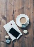 Tasse Kaffee und blaue Makronen auf Holztischhintergrund Lizenzfreie Stockbilder