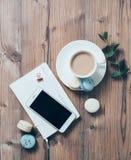 Tasse Kaffee und blaue Makronen auf Holztischhintergrund Stockfotografie
