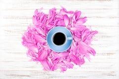 Tasse Kaffee und Blumenblätter von rosa Pfingstrosen auf einem hölzernen Hintergrund Flache Lage Lizenzfreie Stockfotos