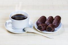 Tasse Kaffee und Bonbons angefüllt mit Pflaumen Stockbild
