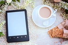Tasse Kaffee und der eBook Leser auf einer Tabelle Stockbild