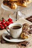 Tasse Kaffee und Eclairs Stockfotografie