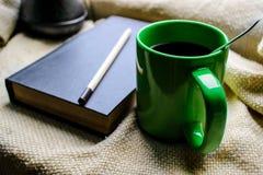 Tasse Kaffee und ein Buch auf einem Fenster Stockfoto