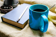 Tasse Kaffee und ein Buch auf einem Fenster Stockbild