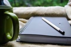 Tasse Kaffee und ein Buch auf einem Fenster Lizenzfreies Stockfoto