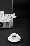 Tasse Kaffee und ein Koffer mit Geld Lizenzfreie Stockbilder