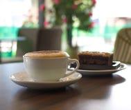 Tasse Kaffee und ein Kuchen auf dem Tisch im Café Stockbilder