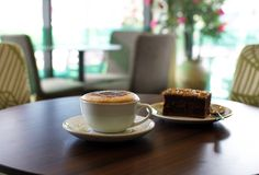 Tasse Kaffee und ein Kuchen auf dem Tisch im Café Lizenzfreie Stockfotos