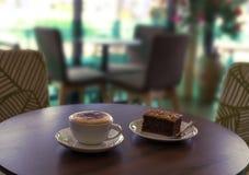 Tasse Kaffee und ein Kuchen auf dem Tisch im Café Lizenzfreie Stockbilder