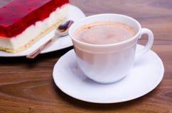 Tasse Kaffee und ein Kuchen auf dem Tisch im Café Stockbild