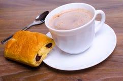 Tasse Kaffee und ein Kuchen auf dem Tisch im Café lizenzfreies stockbild