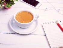 Tasse Kaffee und ein leeres Papiernotizbuch Stockbilder