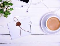 Tasse Kaffee und ein Papier versiegelter Umschlag Stockfoto