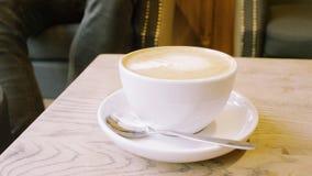Tasse Kaffee und ein Teelöffel Mann, der in der Nähe sitzt Lizenzfreies Stockbild