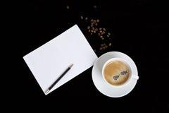 Tasse Kaffee und ein weißes Blatt auf einem schwarzen Hintergrund Stockfoto