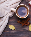 Tasse Kaffee und gemütliches blaket auf hölzernem backrgound Stockbilder