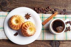 Tasse Kaffee und geschmackvoller kleiner Kuchen Stockfotos